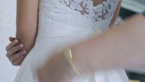 Mulher que amarra a curva no close-up do vestido do ` s da noiva video estoque