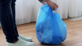 Mulher que amarra o saco com lixo em casa