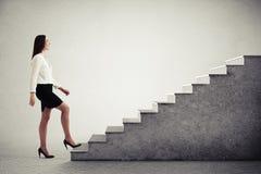 Mulher que anda acima das escadas concretas Fotos de Stock
