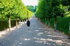 Mulher que anda afastado no jardim francês Imagens de Stock