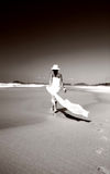 Mulher que anda ao longo da praia imagens de stock