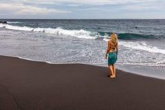 Mulher que anda ao longo da praia preta da areia em Padangbai, ilha de Bali, Indonésia Imagens de Stock Royalty Free