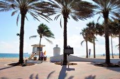 Mulher que anda atrás da estação da salva-vidas na praia Foto de Stock Royalty Free