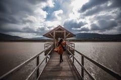 Mulher que anda através da ponte de madeira através do lago na exposição longa do dia nebuloso fotografia de stock royalty free