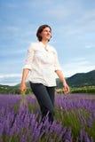 Mulher que anda através do campo da alfazema Foto de Stock Royalty Free