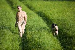 Mulher que anda com cão Imagens de Stock Royalty Free