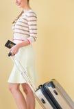 Mulher que anda com passaporte e mala de viagem contra Backgro colorido fotografia de stock