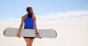 Mulher que anda com placa da areia no deserto 4k filme