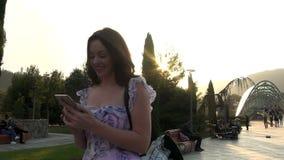 A mulher que anda e que fala com telefone celular, movimento lento, estabilizador da câmera disparou filme