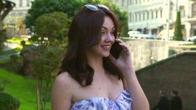 Mulher que anda e que fala no telefone celular, movimento lento, tiro do estabilizador da câmera filme