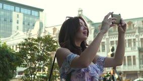 Mulher que anda e que fala no telefone celular, movimento lento, tiro do estabilizador da câmera vídeos de arquivo