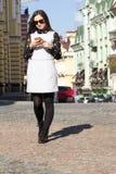 Mulher que anda e que usa o telefone esperto em uma rua da cidade Fotografia de Stock Royalty Free