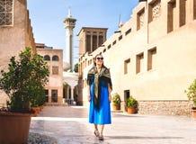 Mulher que anda em Dubai velho, UAE Rua e mesquita árabes tradicionais Turista fêmea na vizinhança histórica de Al Fahidi foto de stock