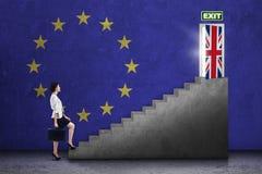 Mulher que anda em escadas para a porta do brexit Fotografia de Stock