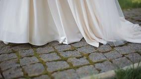 Mulher que anda em sapatas e no vestido vestindo do casamento da estrada do pavimento da pedra Opinião do Close-up grama em um fu filme