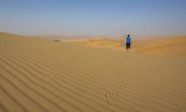 Mulher que anda em um deserto Imagens de Stock Royalty Free