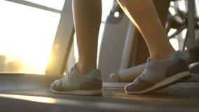 Mulher que anda lentamente na escada rolante, nivelando o exercício no gym no fundo da janela vídeos de arquivo