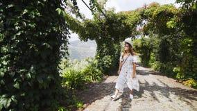 Mulher que anda na aleia com as plantas de videira entre montes filme