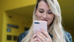 Mulher que anda na cidade e no smartphone dos usos exteriores Moderno bonito, menina do estudante que texting e que usa o app no  filme