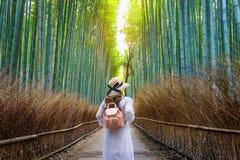 Mulher que anda na floresta de bambu em Kyoto, Jap?o imagens de stock