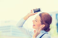Mulher que anda na música de escuta da rua no telefone esperto móvel Fotografia de Stock