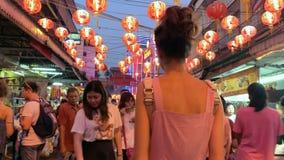 Mulher que anda na noite no mercado de rua iluminado em Tailândia filme