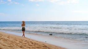 Mulher que anda na praia 4k video estoque