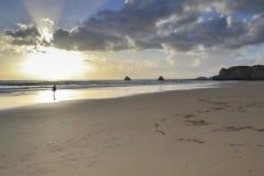 Mulher que anda na praia no por do sol Imagens de Stock Royalty Free