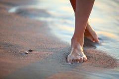 Mulher que anda na praia no por do sol foto de stock royalty free