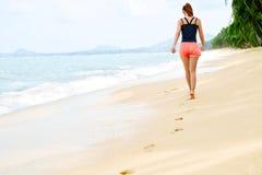 Mulher que anda na praia, pegadas na areia Estilo de vida saudável f Imagens de Stock Royalty Free