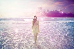 Mulher que anda na praia sonhadora que aprecia a vista para o mar