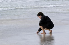 Mulher que anda na ressaca que procura shell do mar Fotografia de Stock Royalty Free