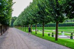 Mulher que anda no jardim francês Imagem de Stock Royalty Free