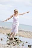 Mulher que anda no sorriso do trajeto da praia foto de stock