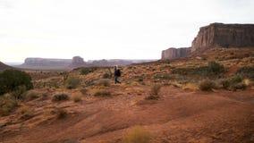 A mulher que anda no vale do monumento com vermelho balança a vista geral video estoque