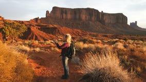 Mulher que anda no vale do monumento que toma fotos com smartphone vídeos de arquivo