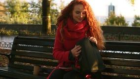 Mulher que anda pelo parque da cidade com café 'togo 'e saco Senhora de cabelo encaracolado que começa ler um livro em um banco d vídeos de arquivo