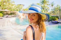 Mulher que anda por piscinas em férias no recurso luxuoso foto de stock