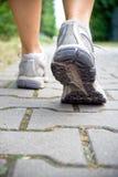 Mulher que anda, sapatas do esporte Imagem de Stock