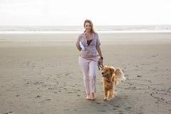 Mulher que anda seu cão Fotos de Stock