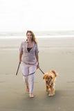 Mulher que anda seu cão Imagens de Stock
