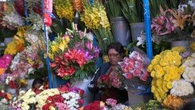 Mulher que apara flores no mercado de San Pedro em Cusco video estoque