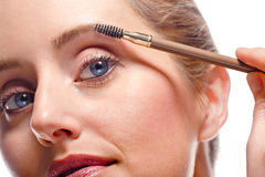 Mulher que aplica a composição usando a escova da sobrancelha Foto de Stock