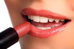 Mulher que aplica cosméticos da beleza do batom aos bordos Fotografia de Stock