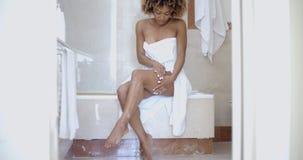 Mulher que aplica a loção do corpo no banheiro Fotografia de Stock Royalty Free