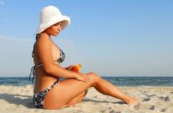 Mulher que aplica a loção do suntan Imagem de Stock Royalty Free