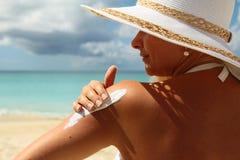 Mulher que aplica a loção do suntan na praia imagens de stock royalty free