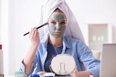 A mulher que aplica a máscara da argila com escova em casa fotografia de stock royalty free