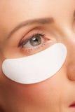Mulher que aplica a máscara de olho do gel Imagem de Stock