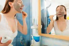 Mulher que aplica a máscara do facial da lama fotografia de stock royalty free